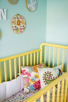 its not the main part of the pic but i noticed it and I love the idea...using old embroidery hoops with material in them as wall hangings for the baby's room!!!