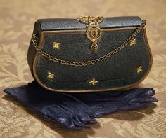 """French Miniature Accessories for Poupee 4"""" (10 cm.) L. case. Including a firm-sided leather-covered case with shaped sides,ormolu accents and clasp,chain handle,opening on one side to rose-silk lined interior with mirror,thimble and pin cushion,and on the other to silk-lined folio. Along with a pair of black kidskin gloves with scalloped edge and stitched thumbs. Excellent condition. French,circa 1875."""