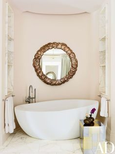 An 18th-century mirror is mounted above the Waterworks tub in one of the master suite's baths; the cube table is vintage Paul Evans | archdigest.com