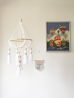 White tassel mobile - boho nursery by Chief Thundercloud! Handmade yarn tassel mobile made with pompom trim, rattan/cane hoop, wooden beads and copper and brass accents in white. Please see fourth photo for tassel bead options. Each mobile is made to order and is made and assembled by hand with care and consideration. All tassels are made and tied by me and the pompom trim is hand stitched to the rattan hoop. Due to the handmade nature of this product, slight variations may occur to m...