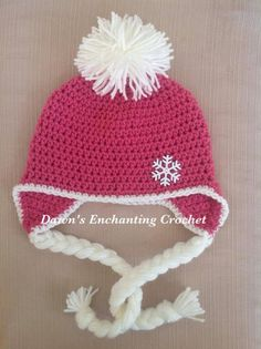Crocheted pink and white snowflake hat with ear flaps and tassels an a Pom Pom.