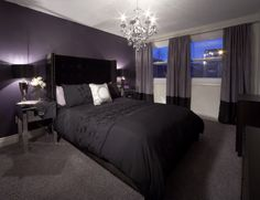 Bedroom with purple feature wall and drapery, crystal chandelier and black bedspread - LUX Design