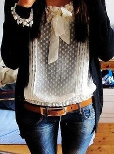 White seethrough shitr with bow at the top black longsleeve flanle jacket cute pearl bracelet dark wash skinny jeans with brown belt..