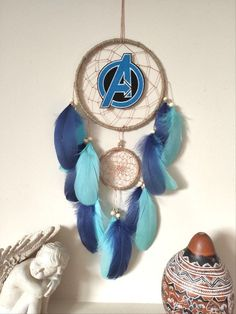 Avengers room wall decor dream catcher Gift for boy// Boy's room decor Dream catcher perfect for boy's room Hang it on the wall or next to your bed, it will be the perfect decor for your room Measurements: Dreamcatcher ring 6 inches across 18 inches length ( not including cotton hanger) Avengers Symbols, Avengers Room, Dream Catcher Decor, Goose Feathers, Room Wall Decor, Dream Decor, Gifts For Boys, Wooden Beads, Decorative Objects