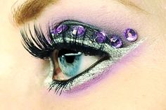 Purple jewels accent lilac and silver glitter lined eye makeup.