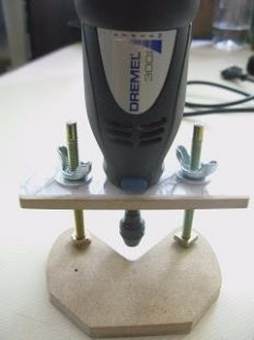 Dremel Router Base - Homemade Dremel router base constructed from particle board, screws, plastic sheet, and wing nuts.