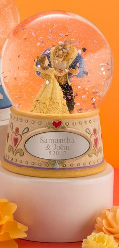Relive the romance of Belle and the Beast with a personalized Jim Shore Disney Traditions Beauty and the Beast Snow Globe. This stunning snow globe is designed by world-renowned artist Jim Shore. Shore's work is known for combining folk art themes with a vibrant color pallet.