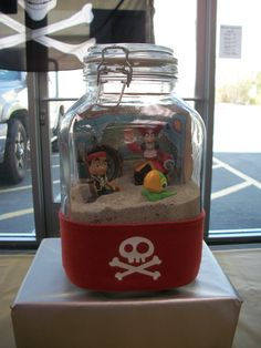 Jake and the Neverland Pirates decoration.  Fill a bottle with sand, put in a map for a background, put in characters (or some kind of pirate toy), and wrap with a pirate bandana