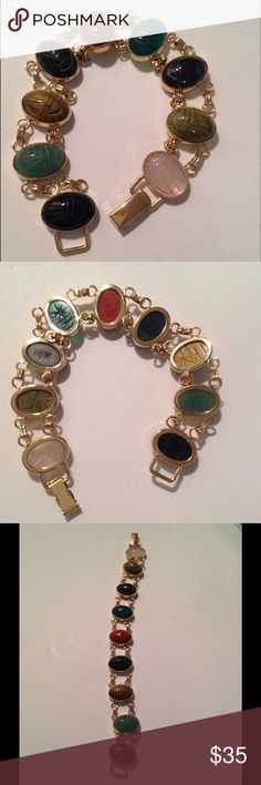 """Vintage Scarab Bracelet Beautiful vintage Scarab bracelet. Bracelet consists of variety of 8 semiprecious stones that are pink Quartz, black onyx, tiger eye, bloodstone, Unakite, chrysoprase, carnelian, jadeite. All set in gold tone metal with a fold over style clasp. Stones are all in great condition with Egyptian hieroglyphics etched on the backs. No markings. Measures 7"""" long Vintage Jewelry Bracelets"""