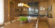 Para uma família que adora receber os amigos na casa de campo, a arquiteta Débora Aguiar investiu em uma decoração rústica, porém sofisticada. A profissional equipou o espaço gourmet com churrasqueira, bancada, cristaleira, mesa e uma bela luminária feita com painel de velas Led.