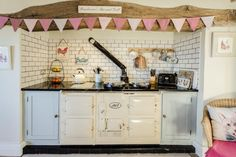 Cottage kitchen Aga, complete with bunting. I Found this on Rightmove.