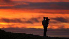 - Pai e filho assistem o pôr do sol de ontem, em Encinitas, na Califórnia. Foto: Mike Blake / Reuters