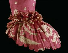 This 1760s gown features a rose-red silk with trails of ivory flowers woven in a complex technique. The gros de tours silk, dates from the 1740s, but the gown was been remade into the style of the 1760s. It may have started out as a fashionable 1740s sack-back gown with 'wing' cuff sleeves popular during that decade. In the 1760s, the garment was restyled with a pleated back. The cuffs were replaced with single ruffles with scalloped edges. V T.433-1967