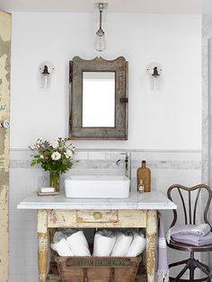 New Purposes for Old Things Sconces by Schoolhouse Electric flank a 1910 medicine cabinet, fitted with a new mirror, in this California ranch's guest bathroom. Bright idea: With the help of a marble top and a Kraus sink set, a weathered table became a washstand.