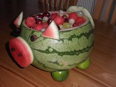 Pig Pickin' Fruit Salad -*- 1  large watermelon * Honeydew and Cantaloupe for variety * green and red grapes * 2 limes (halved for the feet) * raisins for  snout and eyes. * Scoop and ball the melon(s).  Cut snout and ears and use cocktail sticks to hold feet, snout, ears, eyes and tail in place.