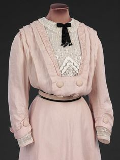 Day dress, HF, ca. 1908. Maker unknown. This pink linen dress bears no makers label, but is likely to be made by a high end dressmaker of the sort employed for less important and less costly gowns. The centre front of the skirt is cut on the cross, giving a graceful hang to the fabric and the dress is trimmed with cotton braid and embroidered striped net. The gilet front adds to the fashionable pouched bodice shape of the Edwardian silhouette.