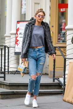 Gigi Hadid stepped out in Manhattan wearing agray Lovers + Friends furry coat, slouchysweater by Grana, Agolde distressed jeans, white Reebok sneakers,an embellishedMoschino bag and cat-eye sunnies.