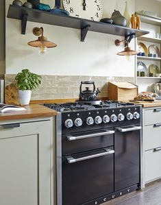 Modern Country style. Splashback: a narrow band of lustrous metro tiles in the same green tone as the cabinetry. Open shelf in charcoal. Copper wall lights