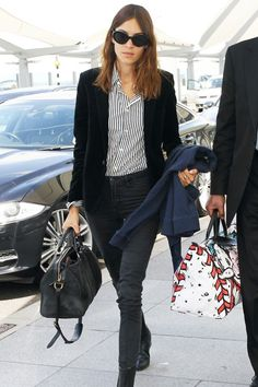 High-waisted black jeans look sophisticated enough to go from the airport to dinner when worn with a blazer, ankle boots and a suede duffel bag.