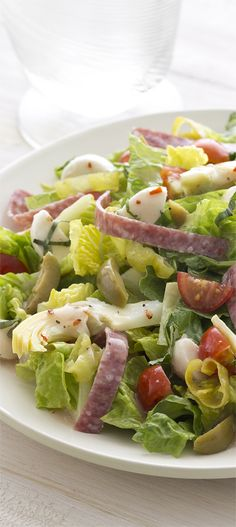 Simply Dressed Light Red Wine Italian Dressing tops this classic Italian salad of Genoa salami, green olives, pepperoncini, mozzarella and artichokes. #MarzettiRecipes