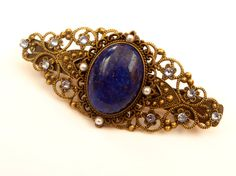 This elegant barrette in antique-style is a beautiful accessory for festive updo. On the back there is a barrettes mechanics with a width of 6.5 cm. The front is decorated with beautiful ornate ornaments made of bronze metal. In the middle there is a jewelry setting with cabochon in dark blue with small glittering particles. The side parts of the hair clip adorned with rhinestones in brand quality in light blue. Also, I have used pearls.    The Barrette has the dimensions 3.5 x 8.2 L B cm…