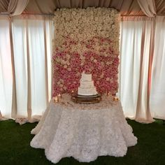 A floral wall behind a wedding cake is sure to be a showstopper.