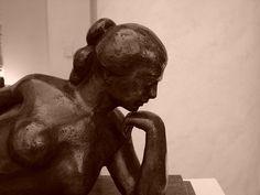 Nu feminino deitado com a mão no queixo, escultura de José Pedrosa
