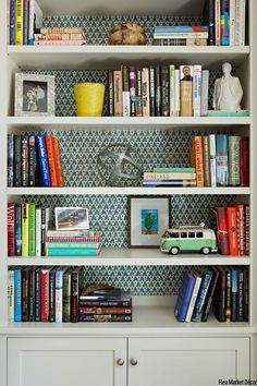 A patterned wallpaper will spruce up any bookshelf. Colorful books and fun accents, like the VW van, invite curiosity as well. Take a look!