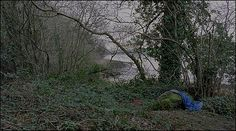 Still from Willie Doherty's Buried (2009) image of a waterway with an item of clothing nearby - image courtesy of the artist
