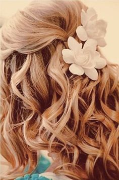 This breezy wedding day hairstyle is optimal for the beach. Ornamented with delightful flowers. #halfupdo #bride #wedding #weddinghairstyle #flowers #curls #beachwedding