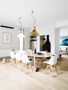 Modern living space with light wood floors, midcentury chairs, and unique light fixtures