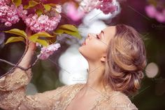 Beautiful sexy adult girl standing at blossoming tree in the garden Photos Sensual young woman standing in sexy transparent dress at blossoming pink sakura tree in the garden by Buyanskyy
