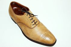 polished driftwood colored crocket and jones leather shoes.