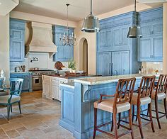 Tuscan kitchens don't shy away from color, whether it's just a dab on the backsplash or a full-on drenching, as in this blue-coated room. In addition to fearless color, the cabinets boast furniturelike touches, including raised-panel doors, intricate trim, carved columns, and regal corbels. And in true Tuscan style, the island doesn't perfectly match the perimeter cupboards, giving the space a harmonized, built-over-time appearance.
