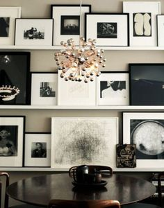 Gallery Wall made up of Black & White framed art & photos, arranged leaning against 3 different shelves. Great way to display your artwork/photos!