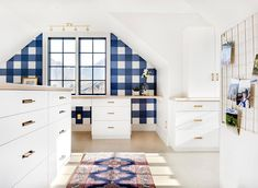 White and blue home office features a pink and blue vintage rug placed in front of white built-in drawers accented with vintage bras pulls and a wood top.