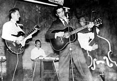 Taken  at the Louisianna Hayride in January 1955. To Elvis' right is Scotty Moore, to Elvis' left, Bill Black. In the back on the steel guitar is Sonny Trammell, a member of the house band.