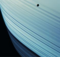 Mimas Transits Saturn's Ring Shadows Saturn's tiny moon Mimas drifts against the backdrop of the planet's northern latitudes. The long, dark lines are shadows cast by Saturn's rings. Just like Earth's atmosphere, Saturn's atmosphere – when relatively cloud-free - can scatter blue light, giving the planet a bluish hue. Mosaic composite photograph. Cassini, 18 January, 2005 Credit: NASA/JPL/Michael Benson/Kinetikon Pictures