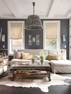 Living room color scheme: dark grey walls, white coffered ceiling, wide white trim, cream colored sofa Living Room Grey, Home Living Room, Living Room Designs, Living Area, Living Room Decor, Cow Hide Rug Living Room, Dark Wood Floors Living Room, Dark Flooring, Small Living