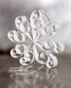 A snowflake ornament is made from eight V-shaped strips of paper, curled at the ends with a quilling needle and joined with a dot of glue at the center.
