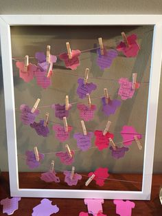 Baby shower clothes line sign-in board! Onesies cut with a criket. All you need an open frame, hemp string, and mini clothes pins.