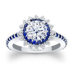 This unique starburst halo engagement ring features a prong set round diamond center encircled with blue sapphires and diamonds set in a starburst pattern. The dainty shank is adorned with shared prong set blue sapphires running down the shoulders for an elegant finish.