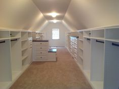 simple and minimalist walk in closet in vaulted roof room small window with white shutter small center table beige flooring system of Dozens of Walk In Closet Organizers Lowes