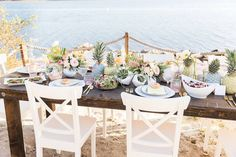 Long wedding table with painted pineapples -tropical wedding centerpiece idea - Check out more beach centerpiece inspiration on WeddingWire! {Cavin Elizabeth Photography}