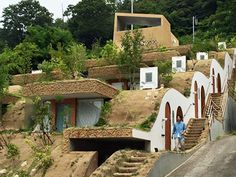"""緑豊かな山を背に傾斜地に""""並べられた""""賃貸住宅。</br>斜面に埋めるという奇抜な設計でありながら、柔らかな曲線と計算されたバランスで、</br>住居は不思議と自然に溶け込むデザインとなっている"""