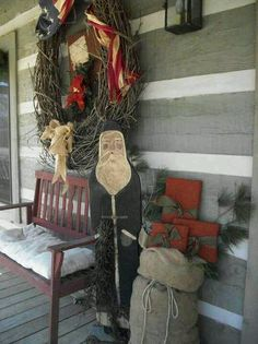 Old Log Cabin...Christmas on the front porch...red bench, wooden Santa, sack of presents, & grapevine wreath.