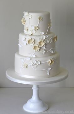 maybe these flower shapes/design, incorporate a little red into flowers, but more a wrap around side look and add a few lady bugs....4 tiers.......and buttercream and edible