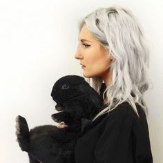 Portrait of artist and illustrator Amy Dover with pet rabbit Shrigley.  Black rabbit grey / white hair.