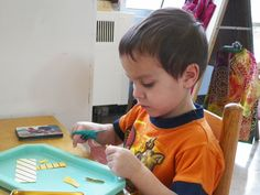 "Working with scissors -  This area of the curriculum focuses on developing skills that allow the child to effectively control and deal with the social and physical environment in which he lives. There is a growing pride in being able to ""do it for myself."" Practical life begins as soon as the young child enters the school and continues throughout the curriculum."