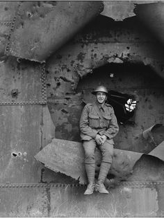 WWI, 30 July 1917; British soldier sitting in the shell-hole in a gasometer at Nieuport. Cropped. © IWM (Q 2642)